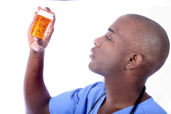 man looking at a bottle of medicine